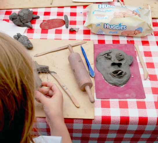 A clay face materialises out of the table...